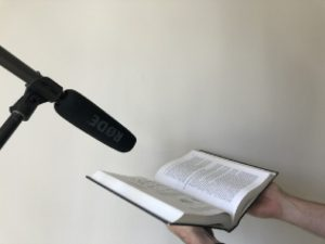 Two hands support an open book next to a microphone.